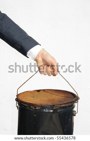 Arm of a man in a suit picking up a bucket indicating manual labor. - stock photo