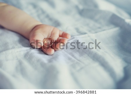arm of a one year old baby with a golden ring - stock photo