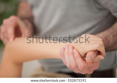 Arm of a woman being manipulated in a room - stock photo