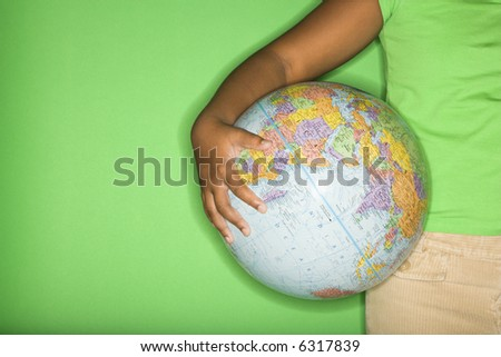 Arm of African American girl holding globe at hip.