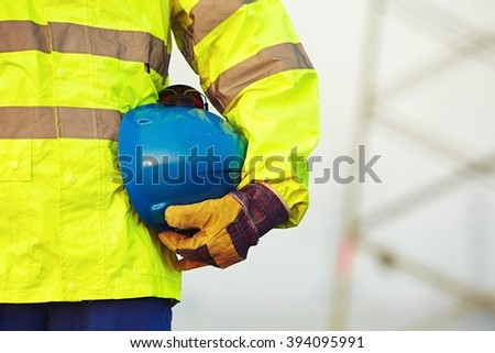 Arm of worker is holding protective helmet - stock photo