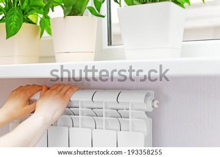Arm put on  heating white radiator.Windowsill with flowers - stock photo