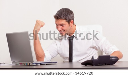 Arm rising happy male chief manager phoning while getting professional career advancement winning lot of money online looking at laptop - stock photo