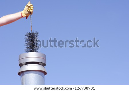 Arm with yellow glove holding sweeper to clean chimney on house, isolated with blue sky as background and copy space. - stock photo