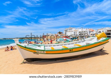 ARMACAO DE PERA BEACH, PORTUGAL - MAY 17, 2015: typical colorful fishing boat on beach in Armacao de Pera coastal town. Algarve region is popular holiday destination in Portugal. - stock photo