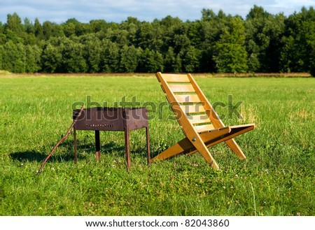 Armchair and barbecue outdoors - stock photo