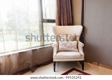 Armchair close to  the window at  a new interiors, through the window  a small garden can be seen.