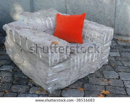 Armchair of blast rock with red pillow - stock photo