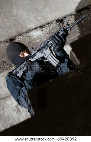 Armed and dangerous man in black uniform aiming the target - stock photo