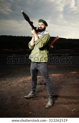Armed and dangerous man with AK-47 handgun and RPG bazooka - stock photo