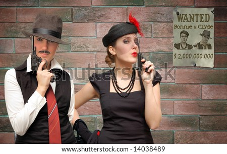Armed Bonnie and Clyde over a brick background - stock photo