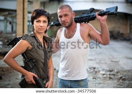 Armed couple with machineguns on the ruined building background.