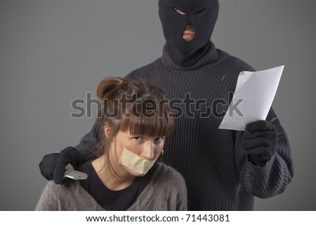 armed hijacker with ransom demand and female hostage - stock photo