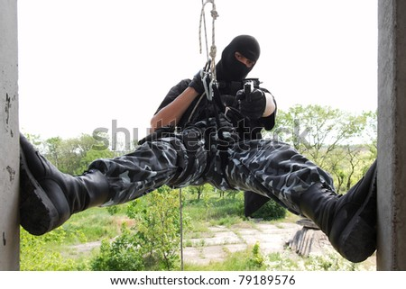 Armed man in military uniform hanging on the rope with a gun in his hand while capturing the building - stock photo