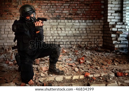 Armed man in protective cask with a pistol on the ruined building background. - stock photo