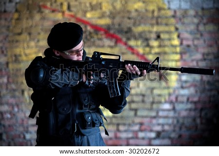 Armed man in protective cask with M4 rifle (with muffler) on the brick wall backround. - stock photo
