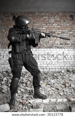 Armed man in protective cask with M4 rifle (with muffler) on the ruined building background. - stock photo