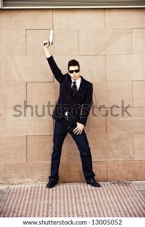 Armed man in sunglasses posing fancy. - stock photo
