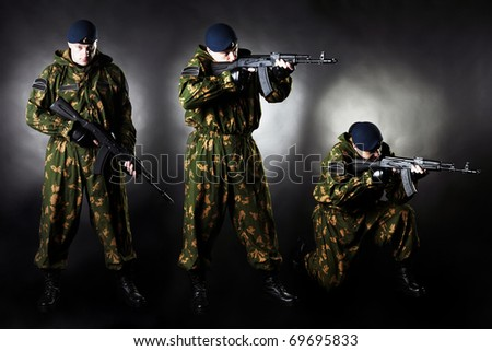 Armed man in uniform on black background studio photo set - stock photo