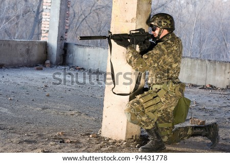 Armed man on his knees aiming at the abandoned building - stock photo