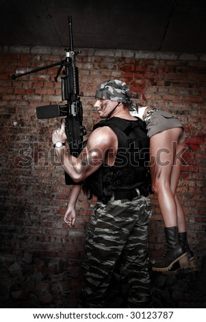 Armed man with light machinegun with the pretty girl on the shoulder on the ruined building back?round.