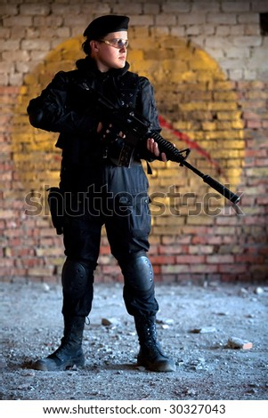 Armed man with M4 rifle (with muffler) on the brick wall background. - stock photo