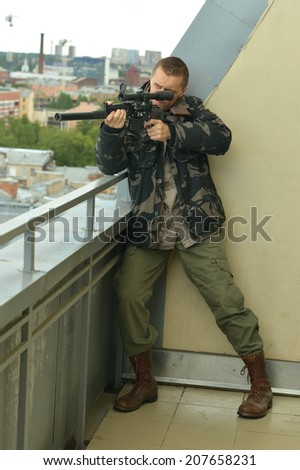 Armed man with weapon aiming from abandoned building - stock photo