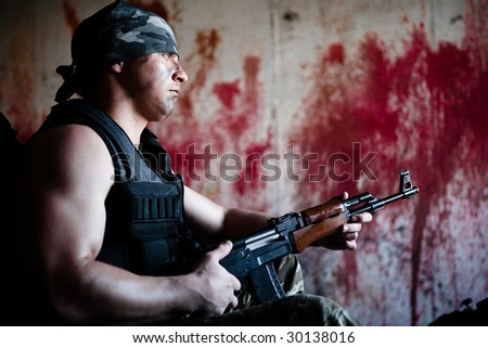 Armed mercenary with 'Kalashnikov' submachine gun on the bloody wall background