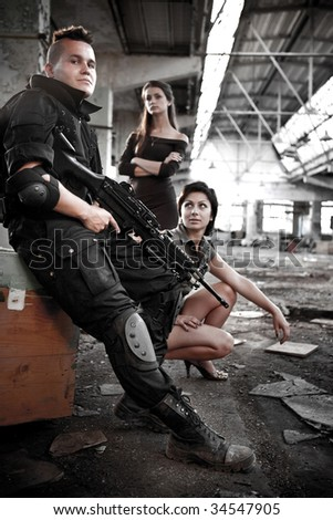 Armed mercenary with machineguns and 2 pretty girls on the ruined building background. - stock photo