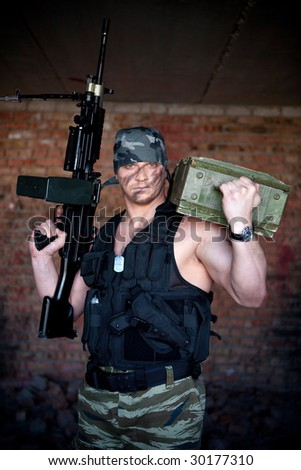 Armed mercenary with submachine gun and box of grenade on the brick wall background