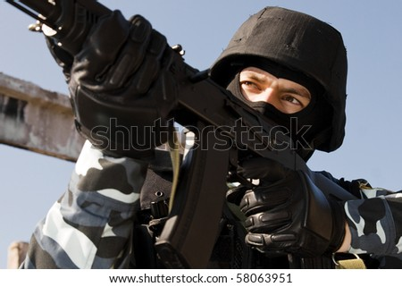 Armed military preparing to shoot with automatic rifle - stock photo