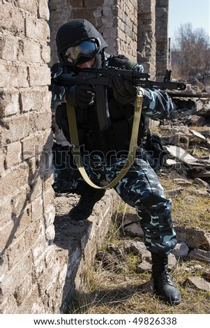 Armed officer in full ammunition targeting with automatic rifle - stock photo
