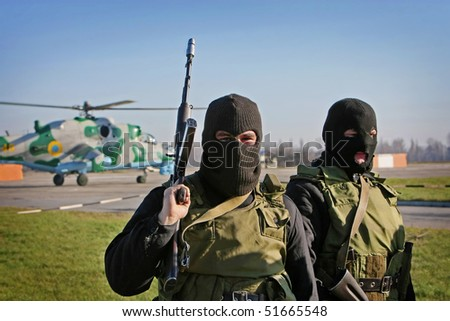 armed people in balaclava mask and helicopter on background