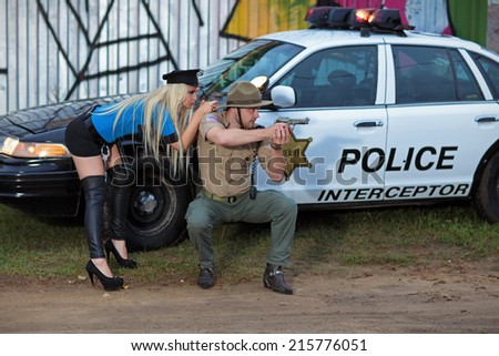 Armed police, a man and woman take measured aim of the gun about his car - stock photo