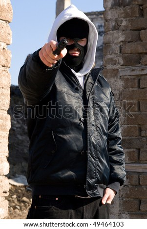 Armed robber pointing at you with his pistol - stock photo