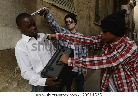 Armed robbery: Gang robbing businessman - stock photo