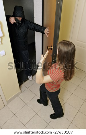 Armed robbery - Robber breaks into a residential building - stock photo