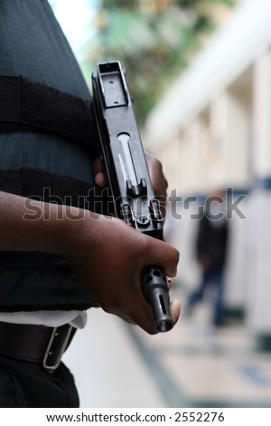 Armed security guard with automatic machine gun, close up - stock photo