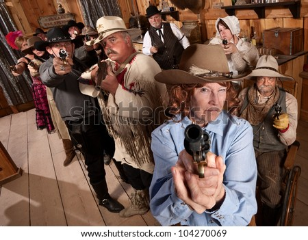 Armed senior woman and crowd points guns in old saloon - stock photo
