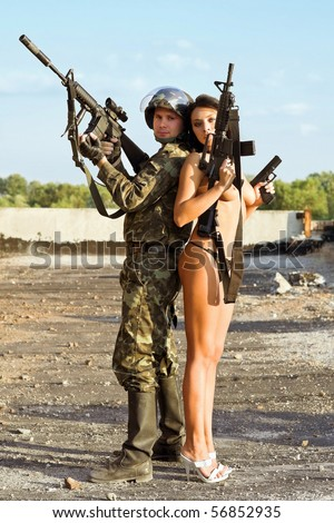 Armed soldier and pretty naked woman with rifle - stock photo