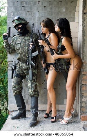 Armed soldier and two sexy women waiting in ambush - stock photo