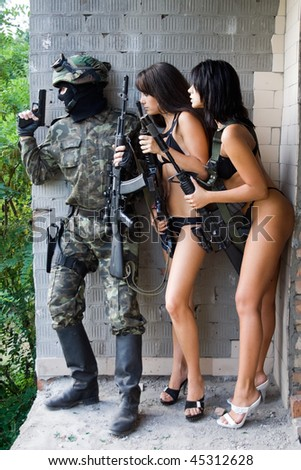 Armed soldier and two young women in ambush - stock photo