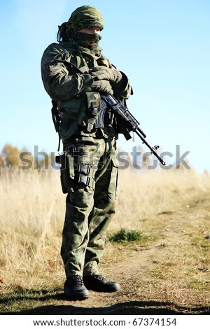 Armed soldier in camouflage is resting after the patrol. - stock photo
