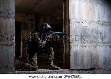 Armed soldier in camouflage, mask and helmet aiming a rifle in a dark room/Armed soldier in camouflage, mask and helmet aiming a rifle in a dark room - stock photo