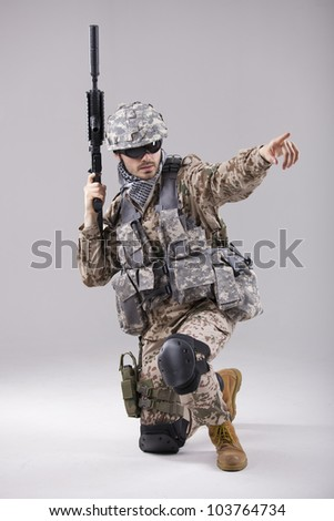 Armed Soldier in camouflage pointing with a finger