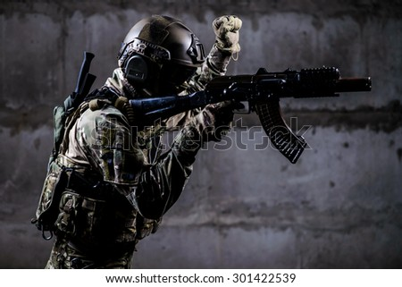 Armed soldier in camouflage with weapon shows special signal/ - stock photo