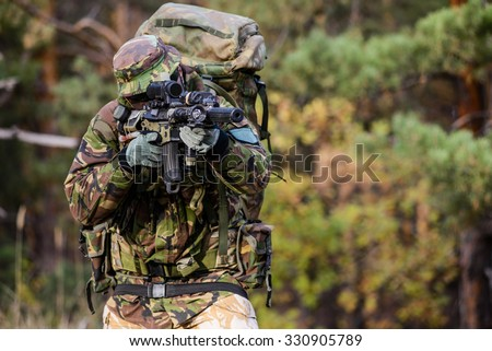 Armed soldier in uniform with assault rifle in forest aiming at target/Soldier on battle field in forest, aiming. - stock photo