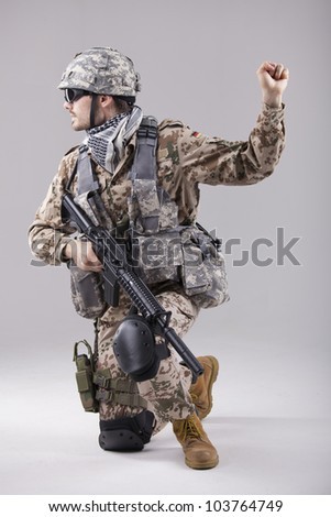 armed soldier kneeling with hand warning or stop gesture - stock photo