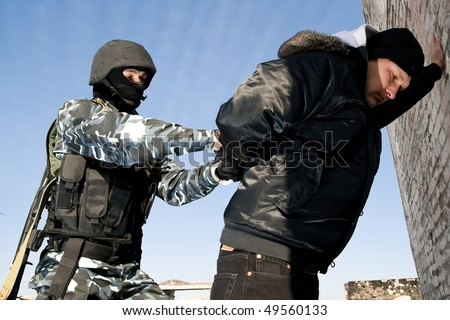 Armed soldier puts handcuffs on criminal element - stock photo