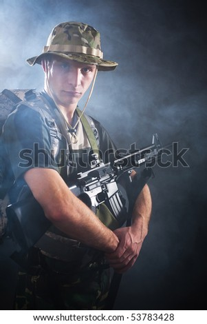 Armed soldier standing in fog.